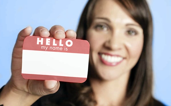 A smiling businesswoman holds up a name tag in the act of introducing herself.
