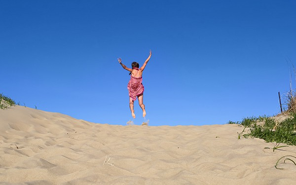 A woman in a pink dress jumps for joy against a backdrop of brilliant warm blue sky and golden sand dunes.